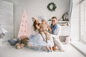 Happy young father mother and baby boy in christmas studio