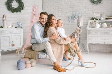 Young happy family with baby in christmas decor studio