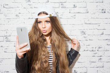 Teenage girl taking a selfie on smartphone against brick wall