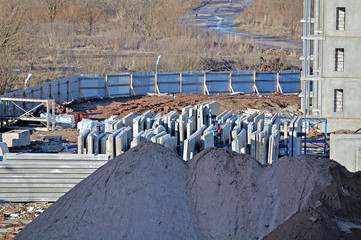Construction site with concrete panels and piles of sand on the foreground