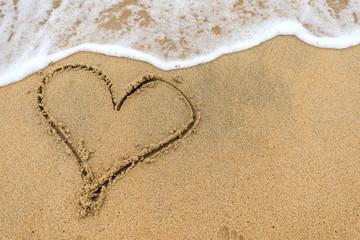 Heart drawn on sand of beach