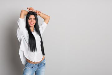 Joyful young girl posing of gray wall