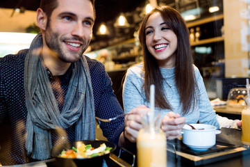 Beautiful young couple eating in restaurant.