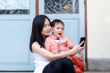 Asian mother and baby boy taking selfie photography