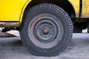 Dirty car tire that has been used for a long time. It is almost out of order and need to be maintenance properly.