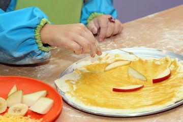 child preparing fruit pizza closeup