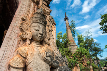 The angel guardian statue standing with the ancient pagoda in Inle lake of Myanmar