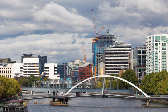 MELBOURNE - JAN 31 2016: View of Southbank footbridge and Yarra river from Princes bridge with office buildings and tower construction cranes in the background.