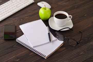 On wooden office desk, stack notepads, smartphone, coffee and mo