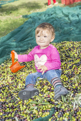 One year old girl on a pile of oil olives
