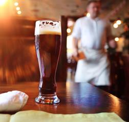 glass of dark beer in a restaurant interior