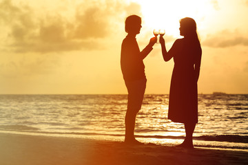 Silhouette of couple drinking wine at sunset beach