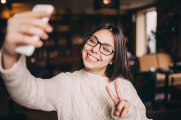 smiling cute asian woman making selfie photo