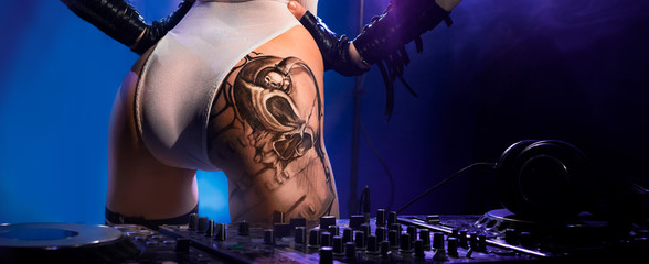 Very nice ass with a tattoo of the girl - DJ, standing near the console with headphones