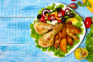 roasted chicken legs with potatoes with Greek salad on wooden background with vegetables