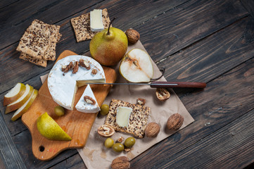 Camembert cheese with walnuts, honey and pears on rustic table. Glass of white wine. Top view