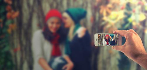 Männliche Hand haltet ein weißes Smartphone und fotografiert damit zwei modische gekleidete Frauen