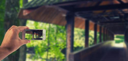 Männliche Hand haltet ein weißes Smartphone und fotografiert damit beim spazierenlaufen eine Brücke