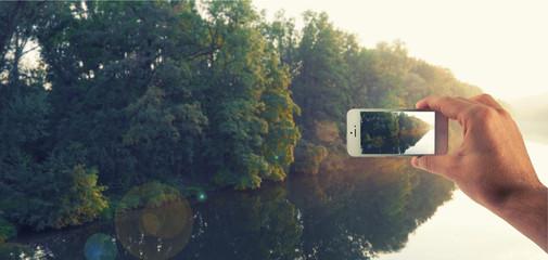 Männliche Hand haltet ein weißes Smartphone und fotografiert damit beim spazierenlaufen einen Fluss