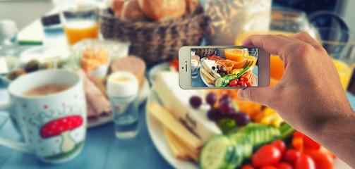 Männliche Hand haltet ein weißes Smartphone und fotografiert damit einen Esstisch mit Kräutern und Vesperplatte