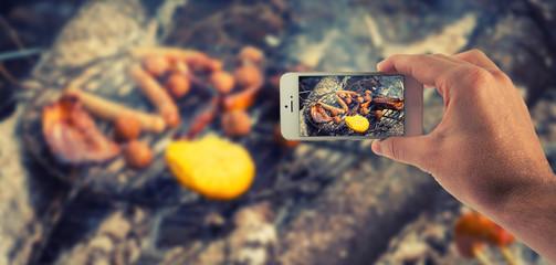 Männliche Hand haltet ein weißes Smartphone und fotografiert damit verschiedene Grillprodukte auf einem Rost