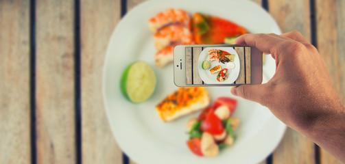 Männliche Hand haltet ein weißes Smartphone und fotografiert damit Essen