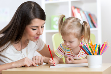 Young mother looking how her kid daughter drawing a picture