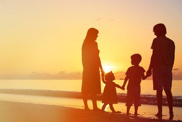 happy family with two kids on sunset beach