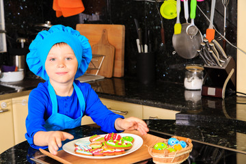 little boy making easter cookies in kitchen