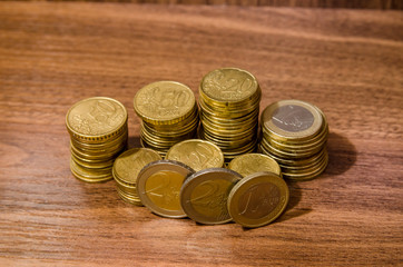 different  golden euro coins on wooden table background