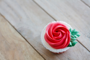 red rose cupcake on wooden table
