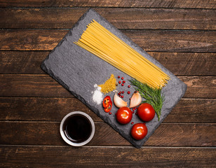 Pasta collection with fresh ingredients on slate board on rustic wood