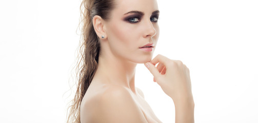 Closeup beauty portrait of young gorgeous woman showing a trendy fashionable dark makeup touching her chin posing with bare shoulders on white studio background