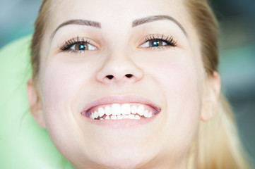 Close-up with beautiful woman face and smile at dentist