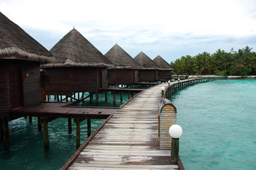 Bungalow and timber pier at island resort Maldives