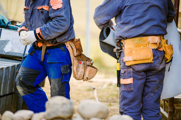 Close up of two construction workers with tool bags