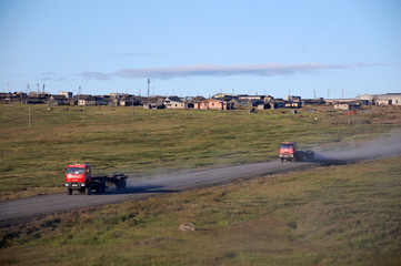 Trucks at gravel road abandoned town Chukotka