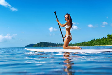 Recreational Water Sports. Healthy Happy Fit Woman With Sexy Body Paddling, Kneeling On Stand Up Paddle, Surf Board In Sea. Summer Holidays Travel Vacation. Active Lifestyle. Leisure Activity. Hobby