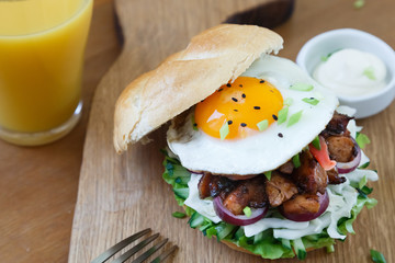 A delicious asian style hamburger garnished with lettuce, onion and topped with fried egg