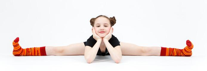 Little girl in black dress doing gymnastic split on white backgr