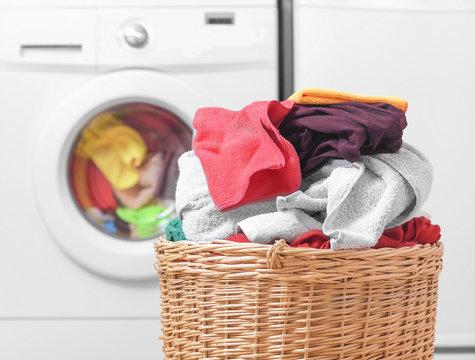 Basket with laundry and washing machine.