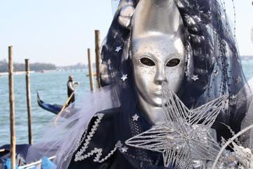 Italy, Venice. Carnival mask in venice posing near the sea