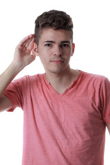 Young caucasian man with his hand to his ear to help hearing