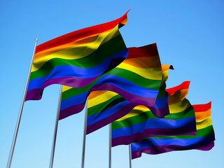 Rainbow flags waving in the wind with a blue sky background. 3d illustration