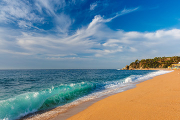 Wall Mural - Sea waves and sand main beach at popular holiday resort Lloret de Mar on Costa Brava in the morning , Catalunya, Spain