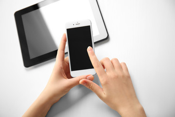 A tablet and female hands using mobile phone, isolated on white