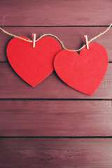 Red felt hearts are on cord against purple wooden background