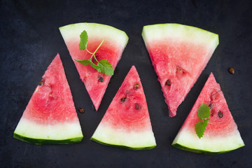 Slices of watermelon on a black background, top view
