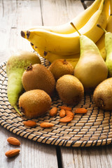 Fruits and almonds on wooden background