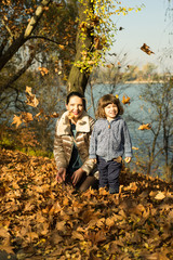 Mother and son playing with autumn leaves